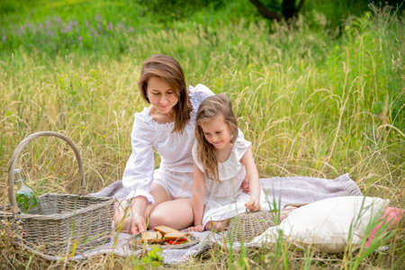 Thirty-year-old beautiful young mother and her little daughter in white dress having fun in a picnic. They are sitting on a plaid on the grass and taking out sandwiches. Maternal care and love. Horizontal photo.