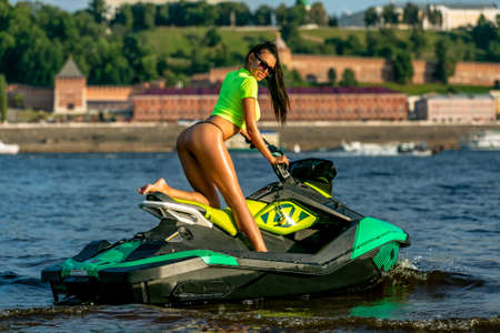 Young brunette in sunglasses and a yellow t-shirt sitting on a jet ski on the river in a sunshine. Summer weekend or vacation. Extreme sport.