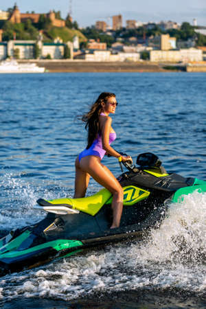 Young girl in a blue swimsuit ride a jet ski on the river in a sunshine. Summer weekend or vacation. Extreme sport.