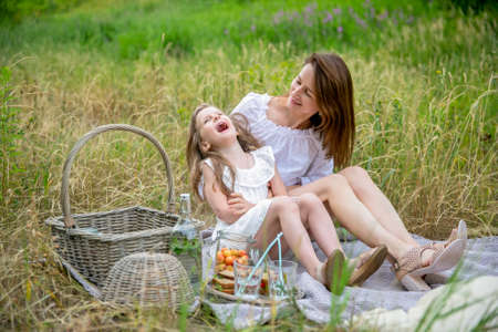 Beautiful young mother and her little daughter in white dress having fun in a picnic on a summer day. They sit on the rug and laugh. Maternal care and love. Horizontal photo.