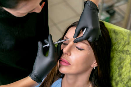 Beautician injects botulinum toxin injections in the womans nose bridge. Middle age woman on cosmetological procedures. Beauty and wellness. Close-up.