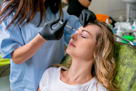 Beautician injects botulinum toxin injections in the womans nose bridge. Young woman on cosmetological procedures. Beauty and wellness. Banco de Imagens