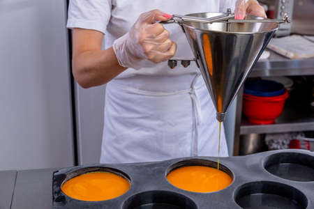 Pastry chef in the kitchen makes passion fruit confit. Cook pours passion fruit confit into the big molds. Master class in the kitchen. The process of cooking. Step by step. Tutorial. Close-up.