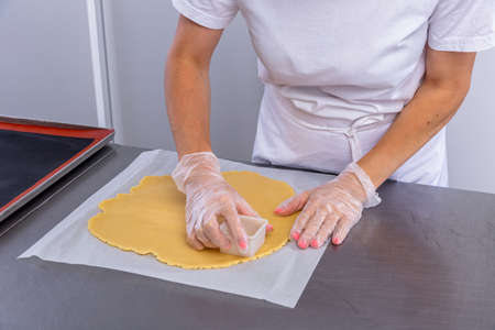 Pastry chef in the kitchen makes cookies. Cook cuts cookies from rolled dough using a cookie cutter. Master class in the kitchen. The process of cooking. Step by step. Tutorial. Close-up.