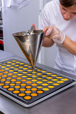 Pastry chef in the kitchen makes passion fruit confit. Cook pours passion fruit confit into the molds. Master class in the kitchen. The process of cooking. Step by step. Tutorial. Close-up.