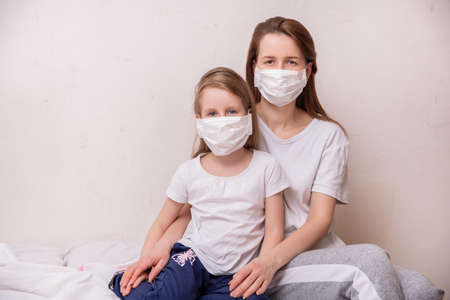 Concept of coronavirus quarantine. Mother and daughter in medical masks protect themselves from viruses and infections. Theme of health and medicine. Standard-Bild
