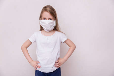 Concept of coronavirus quarantine. Little girl in a medical mask on home quarantine. Theme of health and medicine. Medical virus poster design. Free space for text.