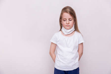 Concept of coronavirus quarantine. Little girl in a medical mask on home quarantine. She took off her mask and looks down sadly. Theme of health and medicine. Free space for text. Stock fotó