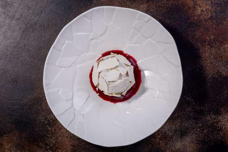 Meringue dessert. The combination of tender meringue, light protein and cream, juicy prunes and almond petals. European cuisine. The work of a professional chef. Dish from a restaurant or cafe menu. Stock Photo