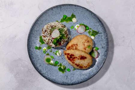 Pike cutlet. Pike fillet, onion, salt, seasonings and spices, side dish of rice and fresh salad, sour cream. European cuisine. The work of a professional chef. Dish from a restaurant menu. Top view.