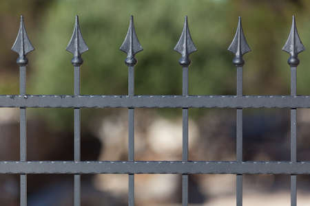 pealing: Detail of a forged metal fence against the blurred background Stock Photo