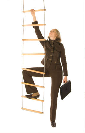 An isolated photo of a businesswoman climbing a rope-ladder Фото со стока