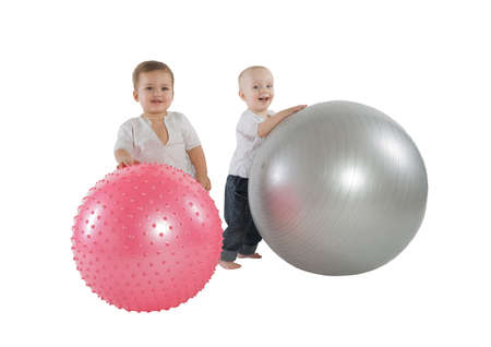 An isolated photo of two boys with fitness balls Фото со стока