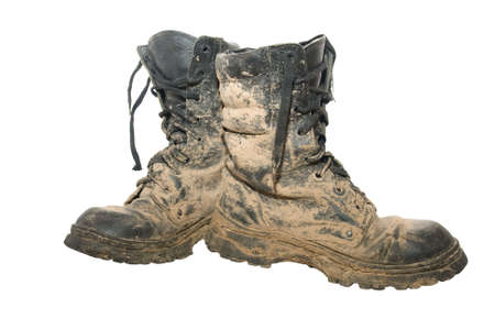 A pair of dirty hiking boots isolated over white