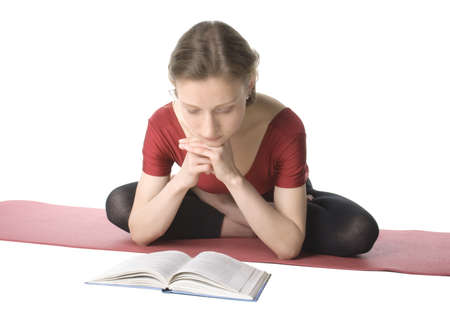 Young woman reading a book sitting in a lotus pose photo