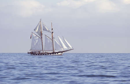 Ship with white sails in the calm sea photo