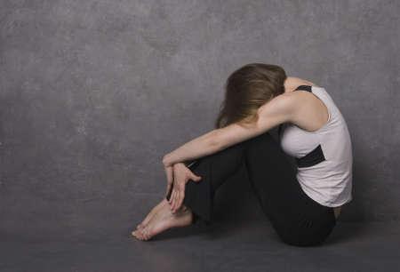 Sad woman sitting on a floor near concrete wall, studio shot Stock Photo - 9040560