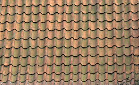 Roof of a house covered with old red tiling photo