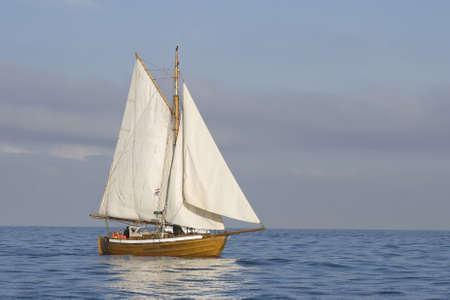 bateau voile: Tender avec des voiles blancs dans la mer calme