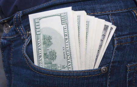 Bundle of dollars in a jeans rear pocket Фото со стока