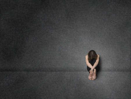 Sad vrouw zitten op een vloer in de buurt betonnen muur, studio shot