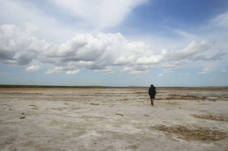 Man with backpack walking among waste landscape, salty lake Baskunckhak in summer Фото со стока