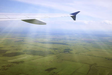 Wing of an airplane and the land below photo