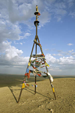 triangulation: Triangulation mark with buddhist prayer flags on a top of a mountain Stock Photo