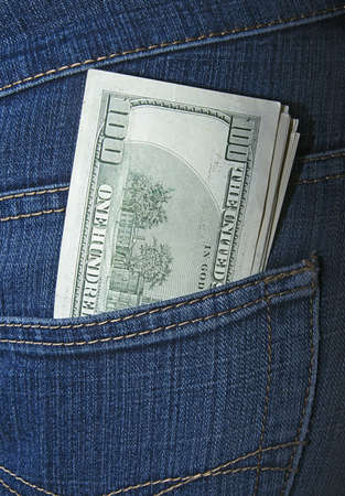 Bundle of dollars in a jeans rear pocket photo
