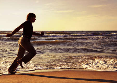 Man running along seashore in summer evening photo