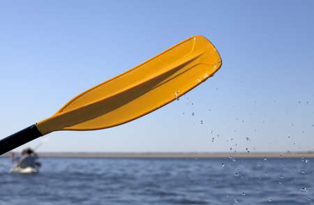 Kayak paddle on side of a boat at still river water photo