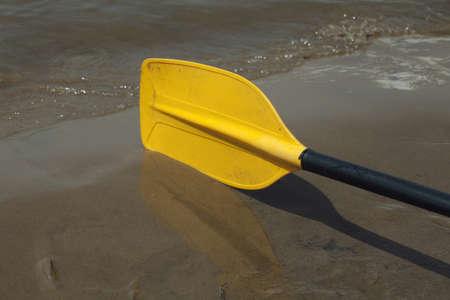 Yellow kayak paddle laying on the wet sand riverbank