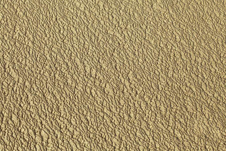 Close-up of rippled wet sand, texture photo