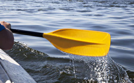Kayak paddle on side of a boat at still river water