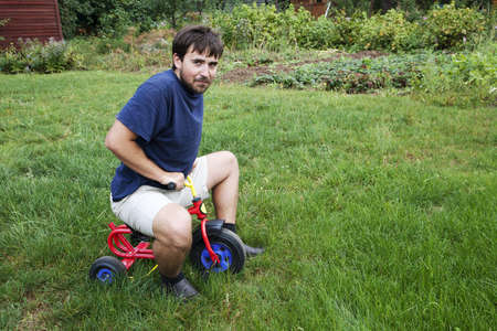 Adult man tying to ride on a small tricycle Stock Photo - 14406196