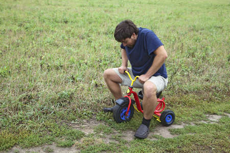 Adult man tying to ride on a small tricycle Stock Photo - 16449238