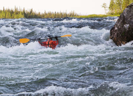 Kayaker turning over in the cataract whitewater