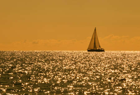 Yacht sailing against sunset. Lonely sail in the evening