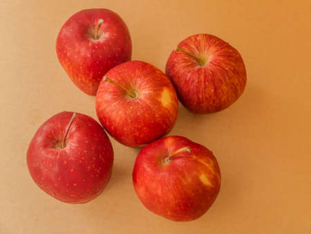 Fresh red apple isolated on brown paper background. photo