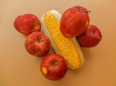 red apples and a corn on brown paper background photo