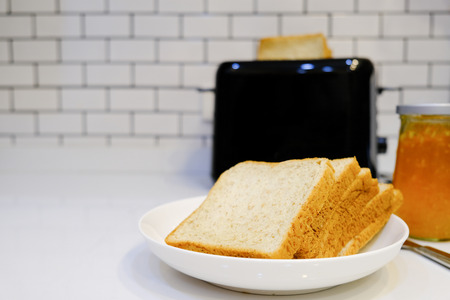 Whole wheat bread on Toaster with orange jam for healthy breakfast at home white brick wall background Stock Photo - 124946805