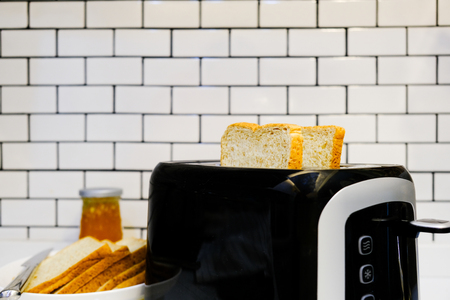 Whole wheat bread on Toaster with orange jam for healthy breakfast at home white brick wall background