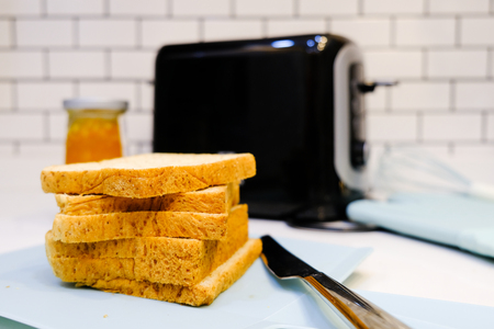 Whole wheat bread on Toaster with orange jam Bottle for healthy breakfast at home white brick wall background Stock Photo - 124946812