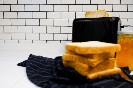 Whole wheat bread on Toaster with orange jam Bottle for healthy breakfast at home white brick wall background Stock Photo