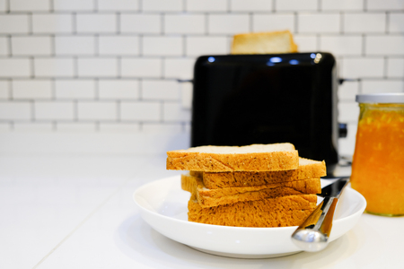 Whole wheat bread on Toaster with orange jam Bottle for healthy breakfast at home white brick wall background Stock Photo - 124946818