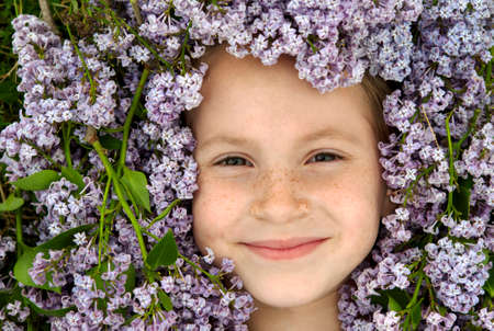 lilacs: Smiling young girl face surrounded by purple Lilacs Stock Photo