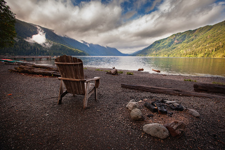 camp fire: Empty wooden chair next to a burnt out camp fire beside Lake Crescent.