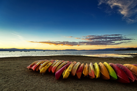 SOUTH LAKE TAHOE, CA - OCTOBER 7, 2015: Kayaks on the beach at South Lake Tahoe at sunset. Editorial