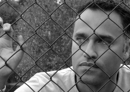 Man standing behind a fence in Black & White Stock Photo