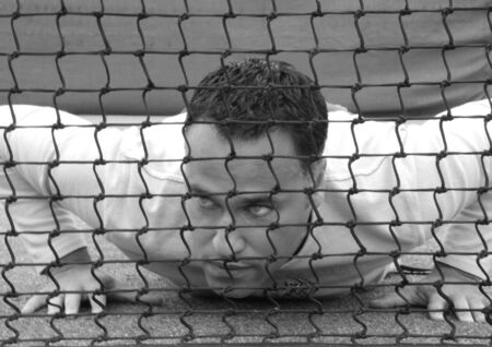 Man Lying on the ground behind a tennis net